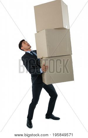 Full length businessman carrying cardboard boxes against white background
