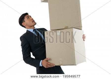 Businessman balancing cardboard boxes while standing against white background