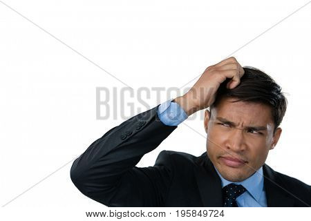Close up of confused businessman with hand in hair against white background