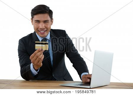 Portrait of businessman holding credit card while using laptop at table against white background
