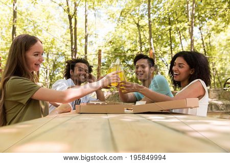 Photo of smiling young multiethnic friends students outdoors drinking juice eating pizza and talking with each other. Looking aside.