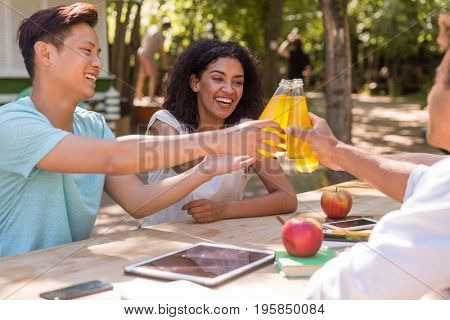 Picture of cheerful young multiethnic friends students outdoors drinking juice and talking with each other. Looking aside.