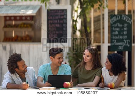Photo of smiling young multiethnic friends students outdoors using tablet computer and talking with each other. Looking aside.