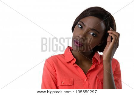 Portrait of confused young woman with hand in hair against white background