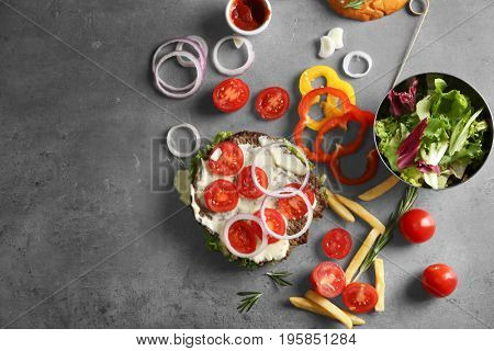 Composition with tasty burger and vegetables on table