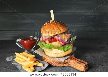 Tasty homemade burger with fries and ketchup on table
