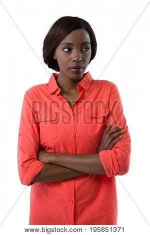 Young woman with arms crossed looking away while standing against white background