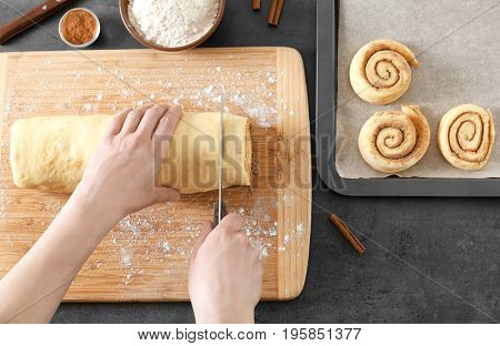 Woman cutting dough for cinnamon rolls on wooden board