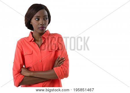 Woman with arms crossed looking away while standing against white background