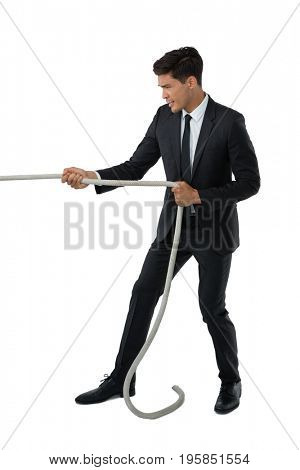 Full length of businessman pulling rope while standing against white background