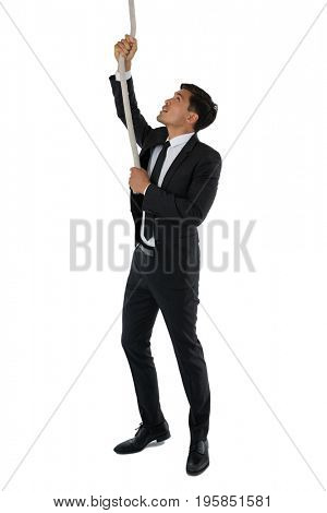 Businessman pulling rope while standing against white background