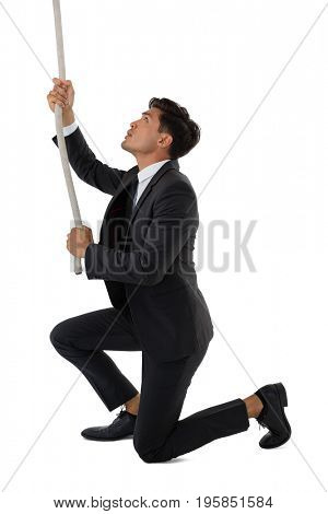 Full length of businessman pulling rope while kneeling against white background