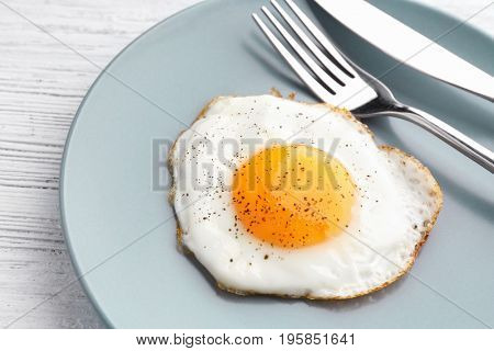 Plate with sunny side up fried egg on wooden table