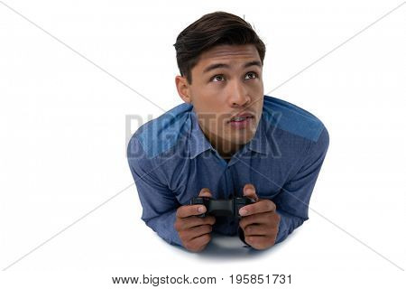 Young businessman playing video game while lying on white background