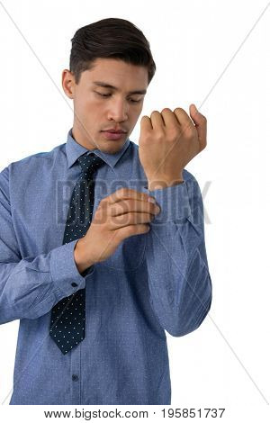 Businessman buttoning cuff while standing against white background