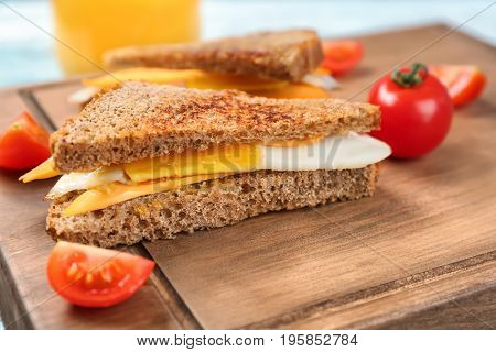 Delicious sandwich with over easy egg and cheese on wooden board