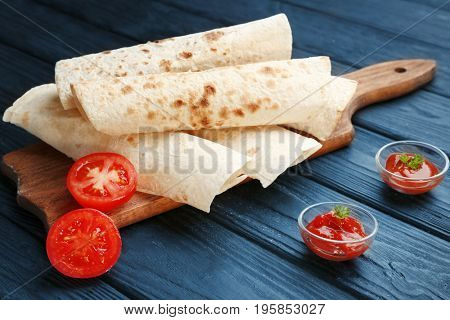 Rolled yummy tortillas with tomatoes and sauce on wooden table