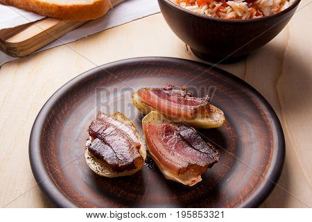 Close Up View Of Baked Potatoes With Slices Of Bacon On Wooden Background. Sauerkraut In Clay Bowl A