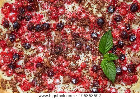 Sweet pizza with currant redcurrant mint and chocolate closeup