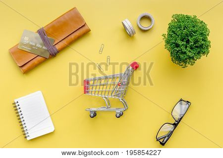 Shopping in online store. Bank card nearby purse, shopping cart on yellow background top view.