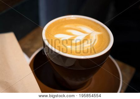 A cup of hot coffee with leaf Latte art