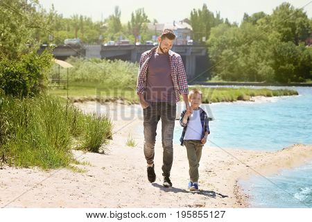 Dad and son walking near river on sunny day