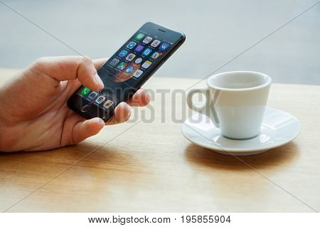 Minsk, Belarus, july 17, 2017: Hand using Iphone with mobile application icons with a cup of coffee on the table, smartphone life style