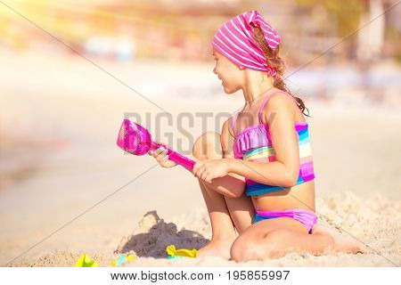 Happy little girl playing on the beach with plastic toys, active childhood, having fun outdoors, enjoying summer holidays on the seashore
