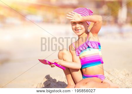 Happy little girl playing on the beach with shovel and sandbag in bright sunny day, active childhood, having fun outdoors, enjoying summer holidays on the seashore