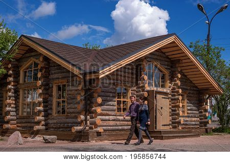 Sortavala, Republic of Karelia, Russia - June 12, 2017: Souvenir shop in a wooden house from logs. In the same house there is the Museum of Ladoga. In the foreground are tourists.