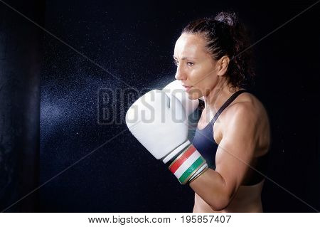 A boxer woman throws a punch in the sack. Splashes of water and sweat on the black background.