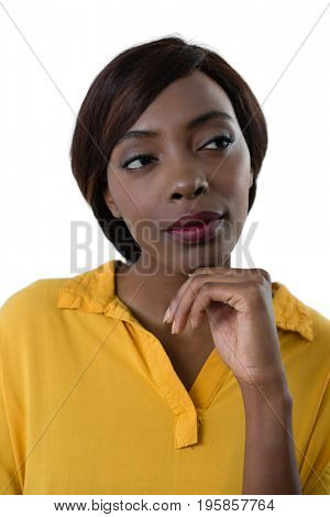 Close up of thoughtful young woman with hand on chin against white background