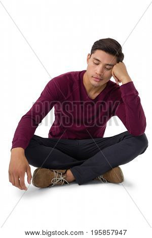 Bored businessman looking down while sitting against white background