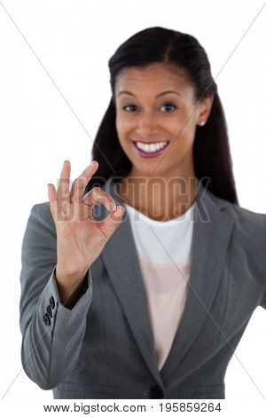 Businesswoman gesturing okay hand sign
