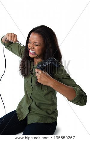 Frustrated woman biting a wire of joystick against white background