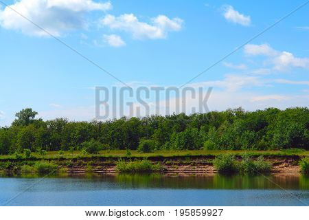 Landscape with clouds in blue sky over river. At the lake a precipitous shore
