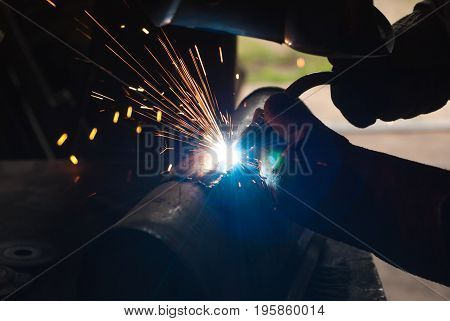 The silhouette of a welder, a tank of oxygen, bright lights and sparks, welding works