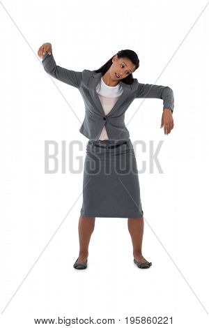 Excited businesswoman dancing against white background