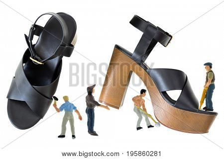 Mini men working on black high-heel shoes with open toe cross strap platform sandals with brown chunky block heel, ankle strap fastens with metal buckle isolated on white