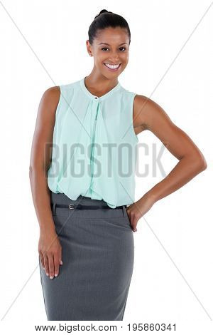 Smiling businesswoman standing with her hand on hip against white back