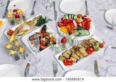 Rolls of aubergines, the table is covered with canapes and various dishes.