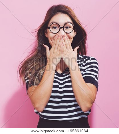 Surprised young woman posing on a pink background