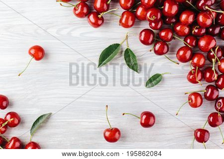 Ripe cherry with leaves on a wooden board. view from above