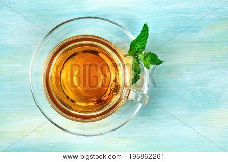 An overhead photo of a cup of vibrant tea with fresh mint leaves, shot from above on a teal blue texture, with a place for text