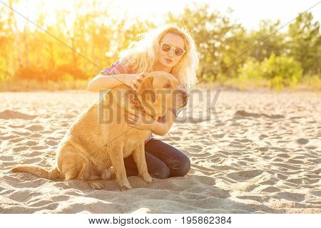 Young woman with her dog at the beach. A young woman sits on the sand with her dog. Labrador. Sun flare