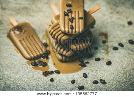 Summer healthy vegan frozen dessert. Flatlay of melting coffee latte popsicles with coffee beans over grey marble background, selective focus
