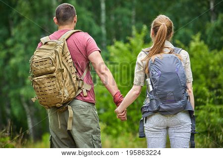 A young man and a girl with backpacks are resting on the nature