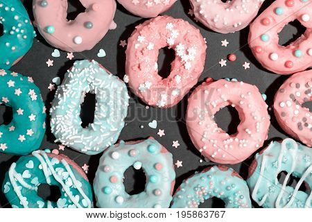 Colorful glazed donuts on a chalky black background