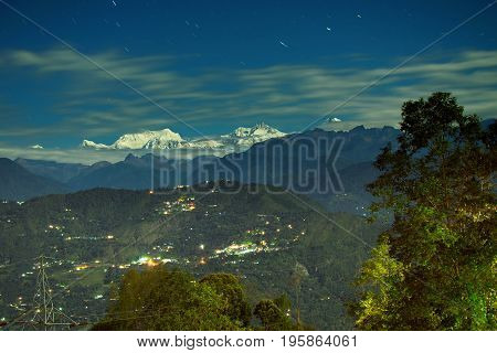 Beautiful view of moonlit Kanchenjungha Mountain Range of great Himalayas shot in a full moon night. Rinchenpong Sikkim India
