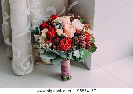 Beautiful wedding bouquet of red flowers, pink flowers and greenery stand on the light background next to the window
